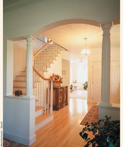 Formal foyer with arch and columns opened to a sunlit set of stairs to the second floor.