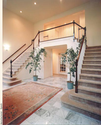 Double staircase with balcony in large open foyer of a modular mansion.
