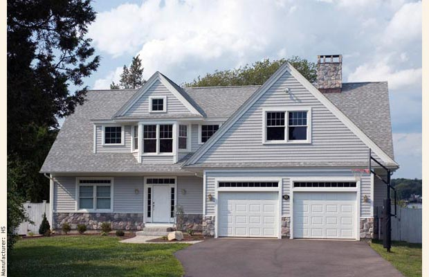An achitect designed cape cod with a front facing garage and gable dormer.