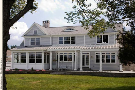 Custom architect designed cape cod modular home with its back facing the lake