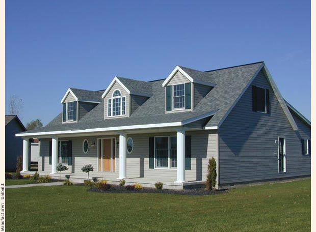 A cape cod modular home with three gable dormers crowning a classic front porch.