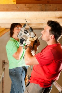 A man and a woman acting as their own modular home general contractor as they work on the ceiling of their home