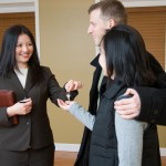 Woman realtor offering key to house to couple