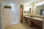 A Universally Designed bathroom with a roll-in shower and knee space under both sinks