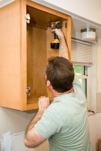 A contractor replacing modular home materials (kitchen cabinets) by installing them on-site