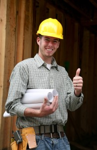A modular home general contractor with his tool belt and blueprints