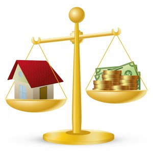 A balance scale calculating a modular home price by comparing the weight of the home to the weight of gold coins