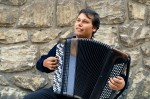 A young man playing an accordion