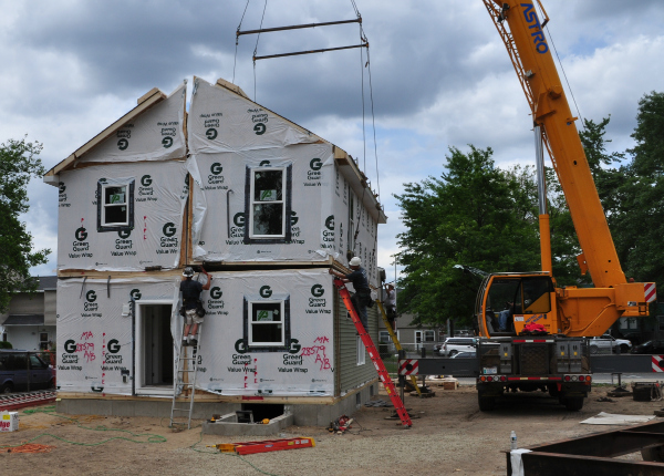 A modular home being set on the foundation. You can learn other things about a dealer's and factory's modular home quality by viewing a home after it has been set on the foundation but before it has been completed by the general contractor.