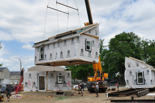 A trained modular home set crew is working with an experienced crane operator to set the 4 modules on this two-story modular home.